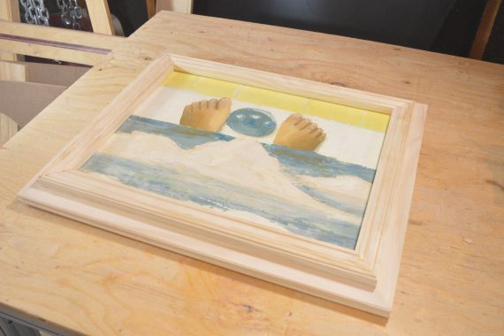 A completed DIY picture frame project, shown with sample art.